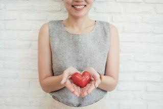 mulher sorrindo segurando um coração