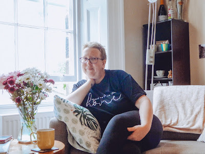Sarah sat on a couch wearing a black t-shirt that says 'There's No Place Like Home'