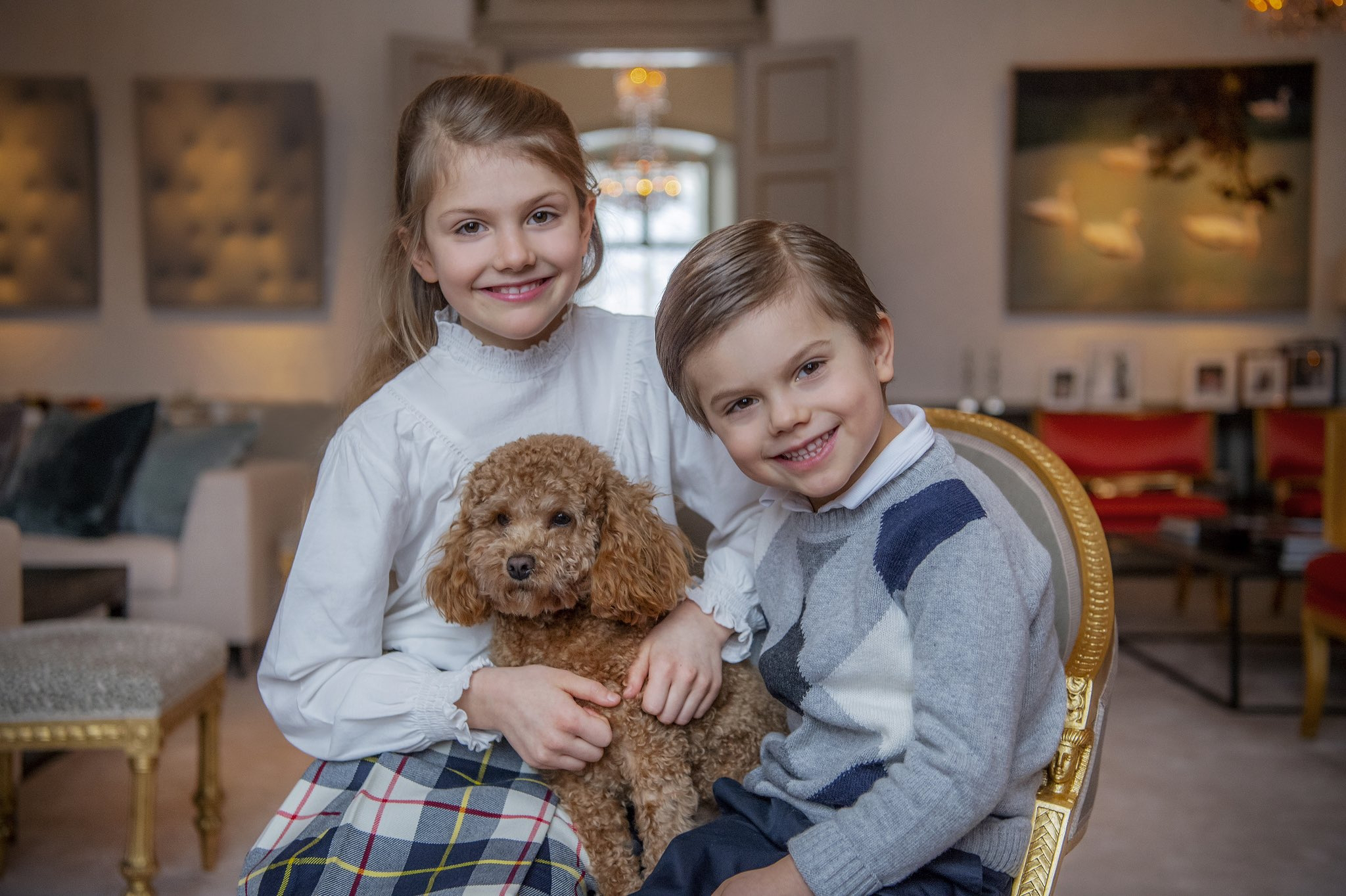 ne picture Estelle is sitting with her younger brother Prince Oscar while holding a pup.