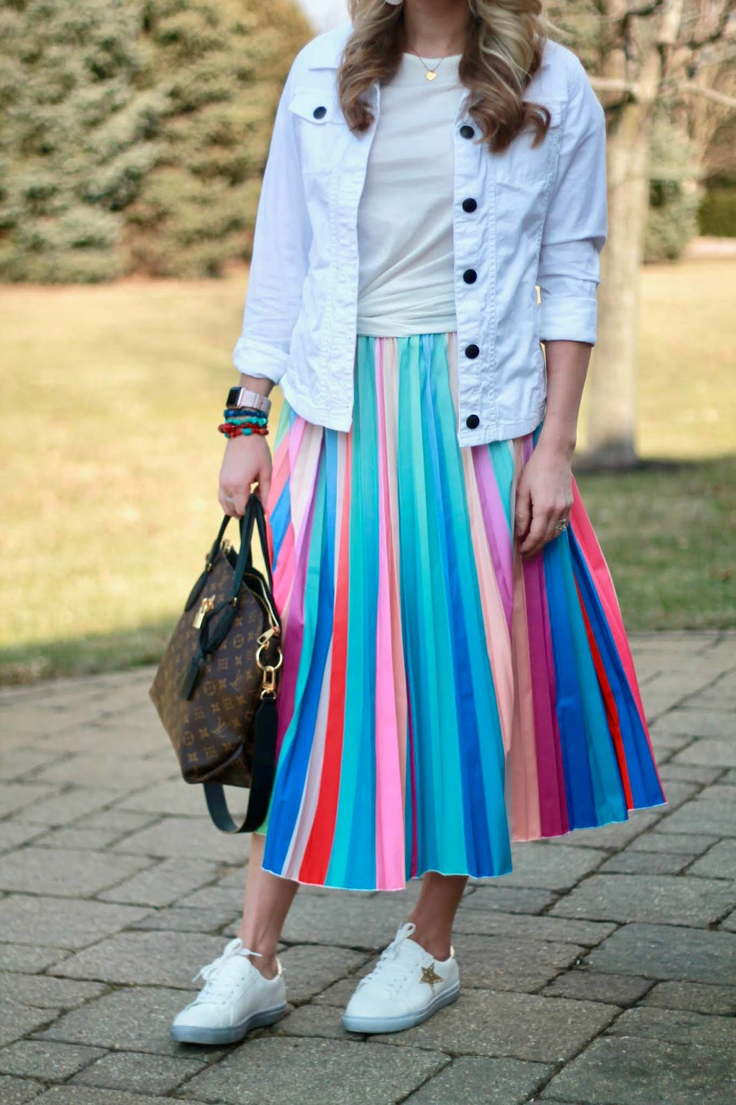 rainbow pleated skirt, pleated skirt 3 ways, cognac leather jacket, LV flower zippered tote, red eyelet blouse, white denim jacket, cognac slouch boots