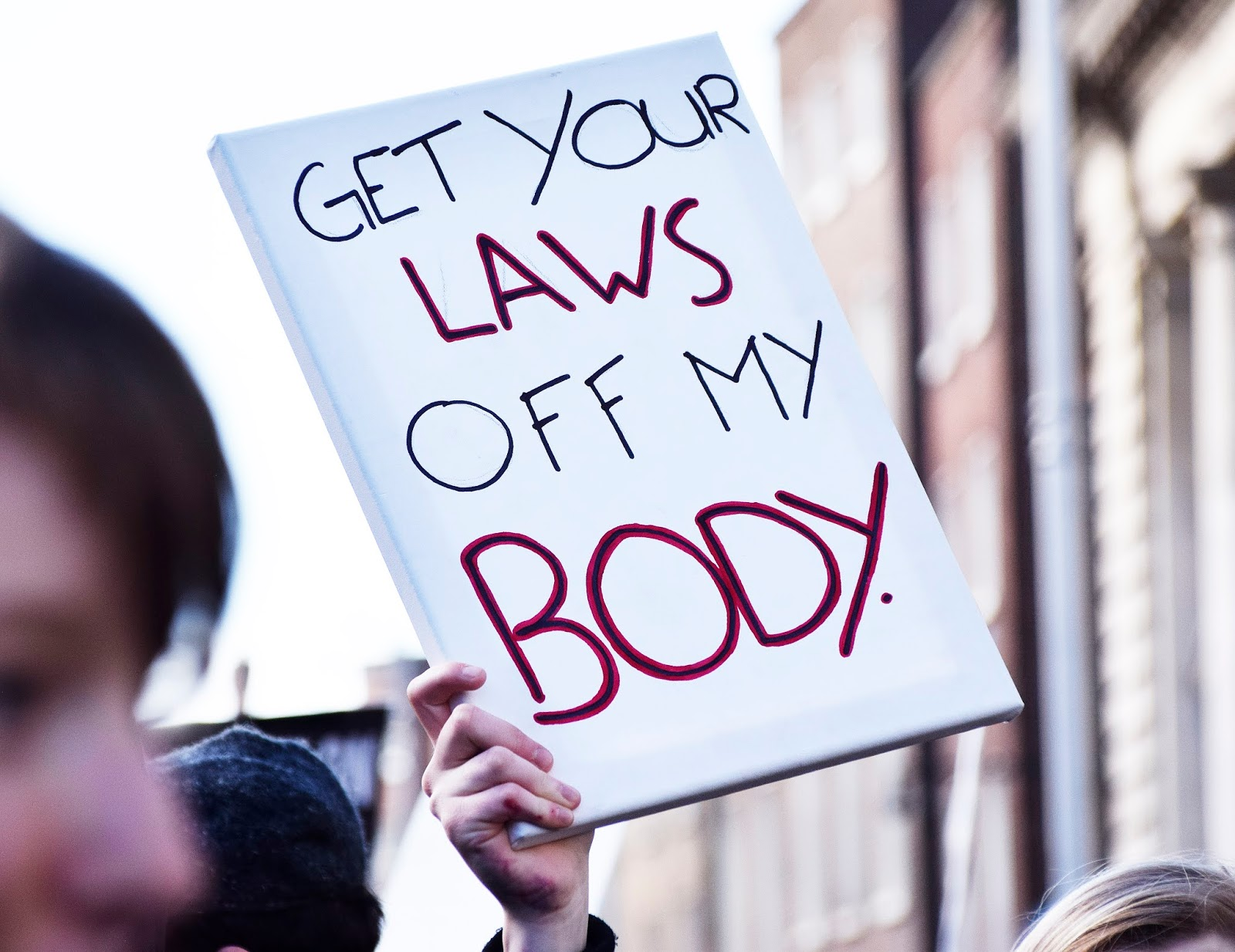 "a protest sign that reads ""get your laws off my body"""