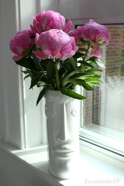 Pink peony bouquet in a white face vase