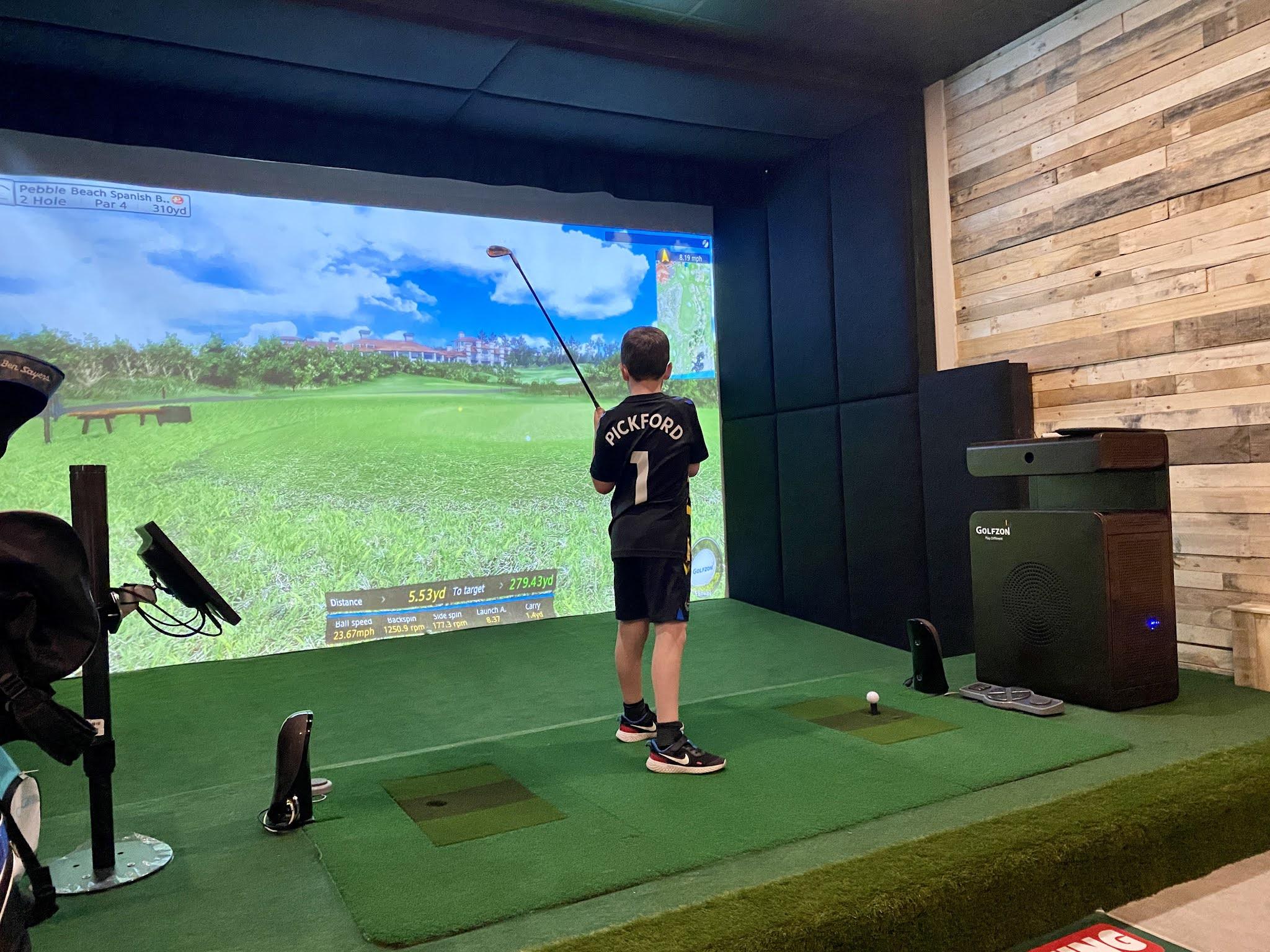 boy playing on a golf simulator