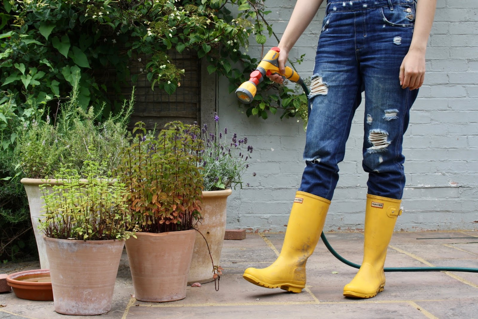 Abbey, visible from the waist down wearing yellow wellies and dungarees, stands next to pot plants in the garden, holding a hose