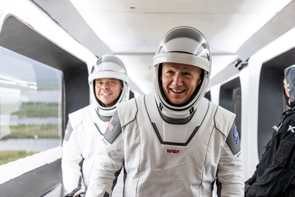 Demo-2 astronauts Doug Hurley and Bob Behnken walk down the Crew Access Arm towards the Crew Dragon vehicle (not visible) for flight at Launch Complex 39A...on May 27, 2020.