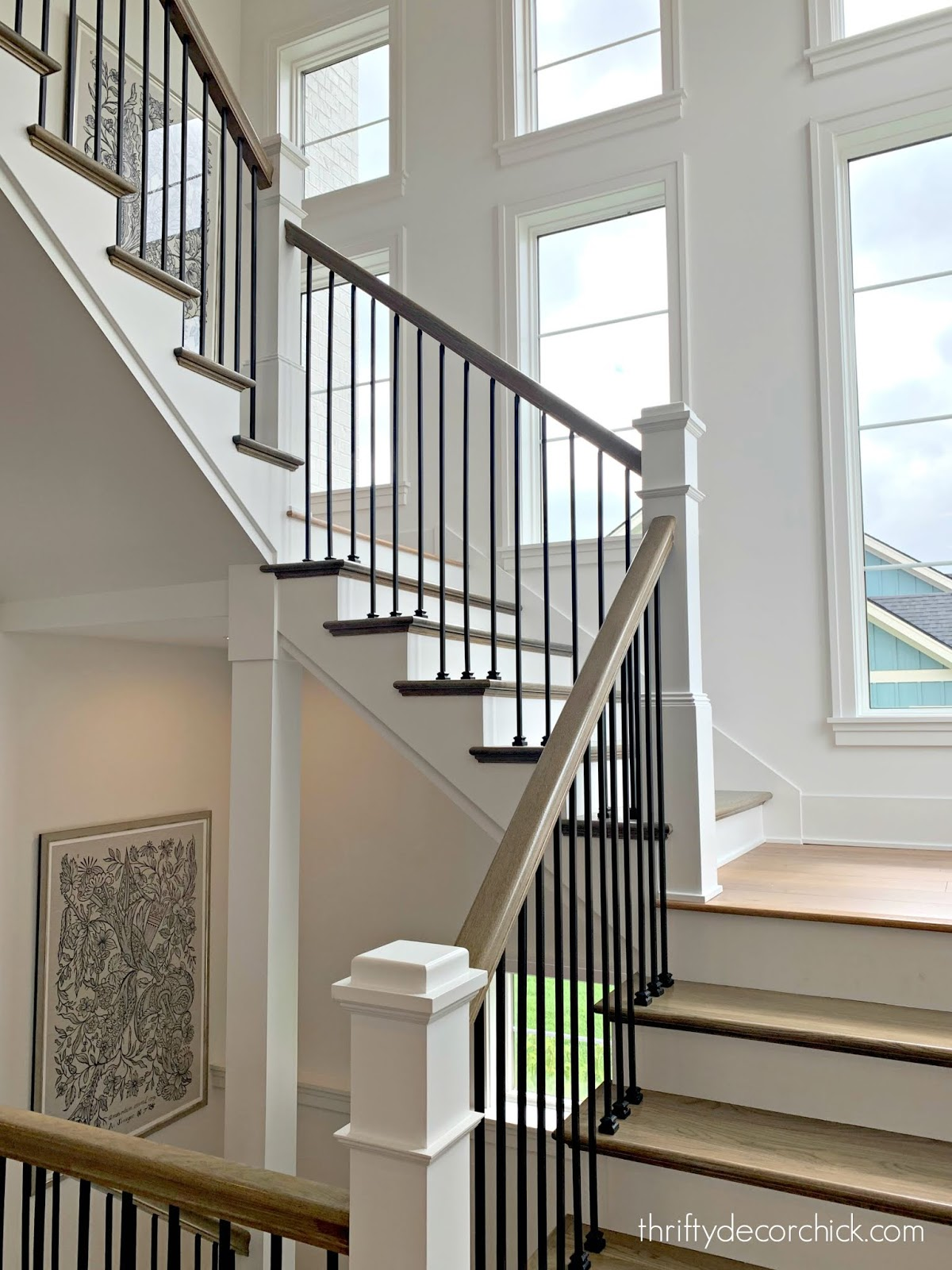 Open staircase with windows and black spindles