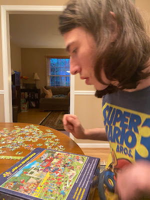 Photo of Jack studying a puzzle box and a puzzle.