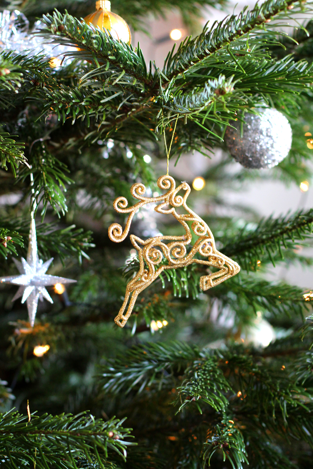 Gold glitter reindeer on our real Christmas tree - UK style blog