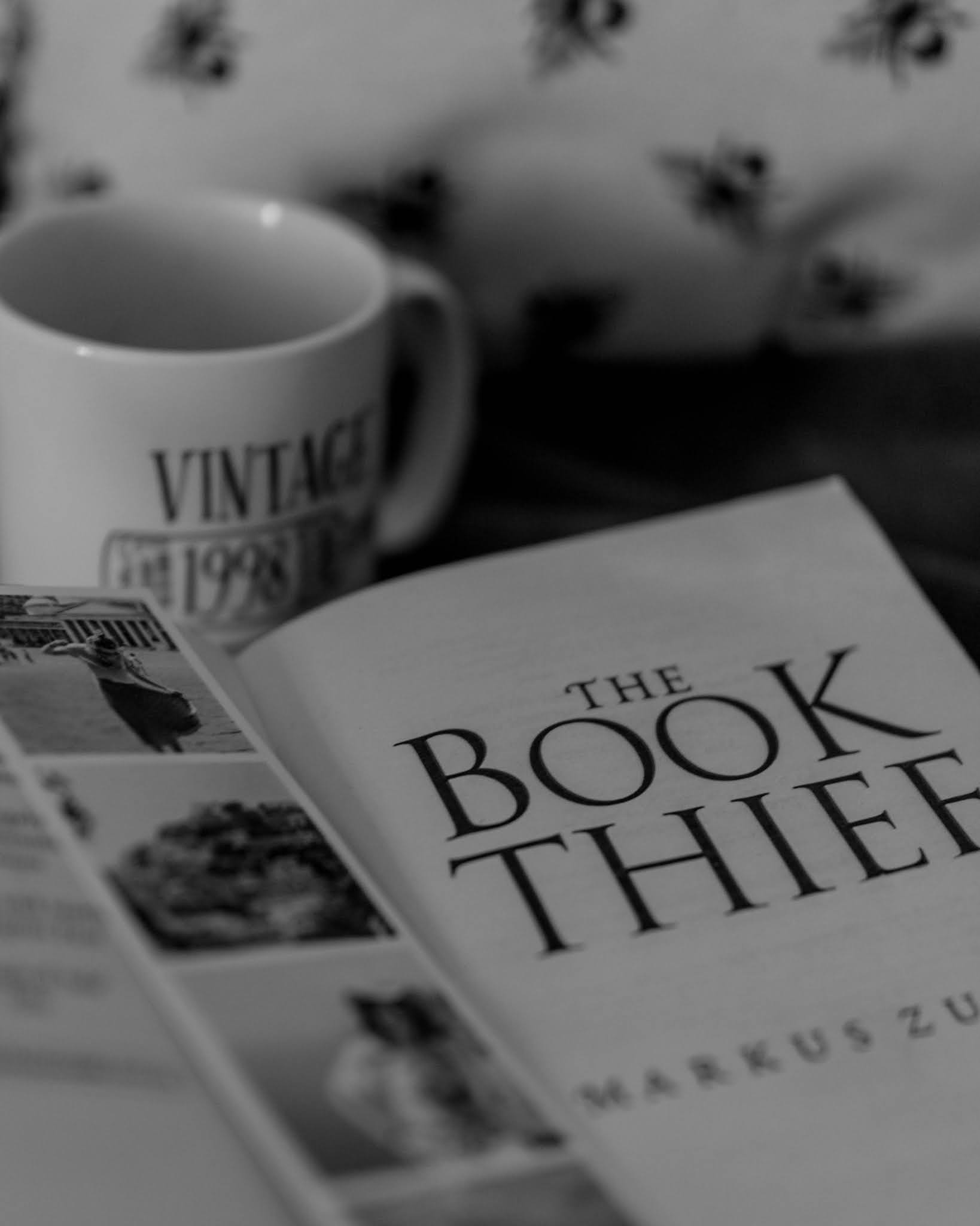 black and white image of open book the book thief by markus zusak with bookmark photostrip and white mug