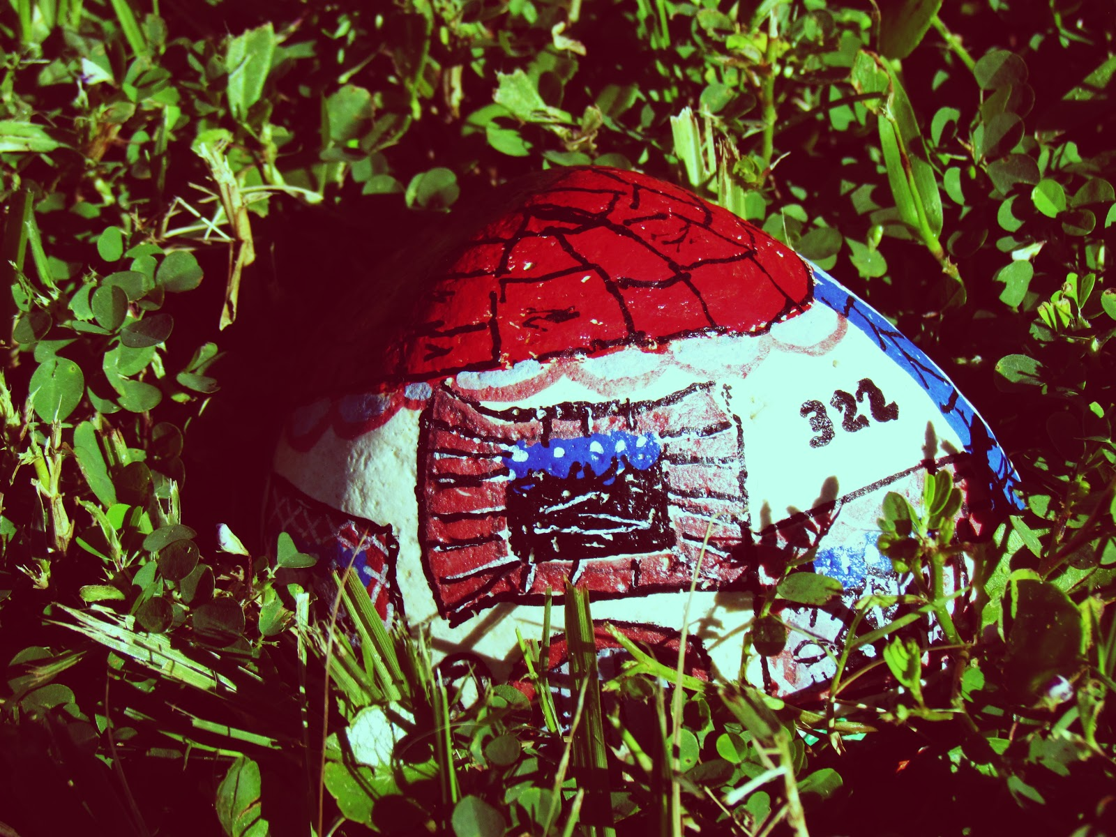 A fairy house painted rock in cute cottage red roof display on green grass in backyard