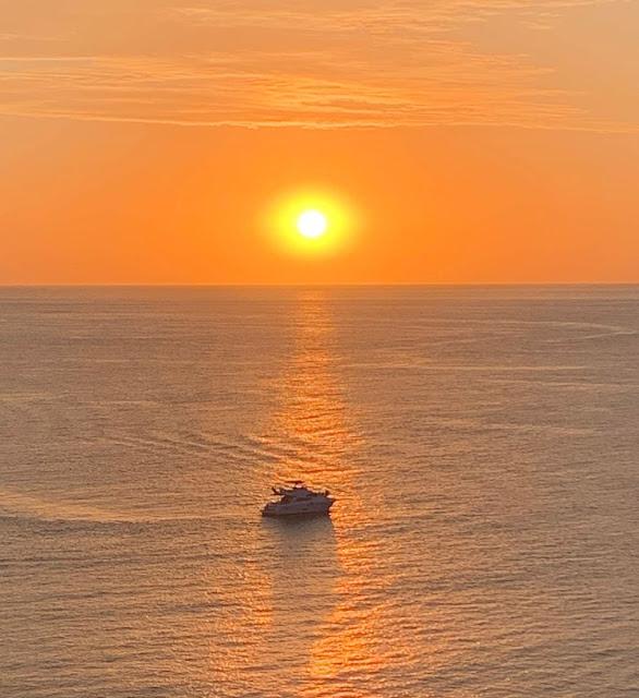 por do sol amarelado e barco no horizonte