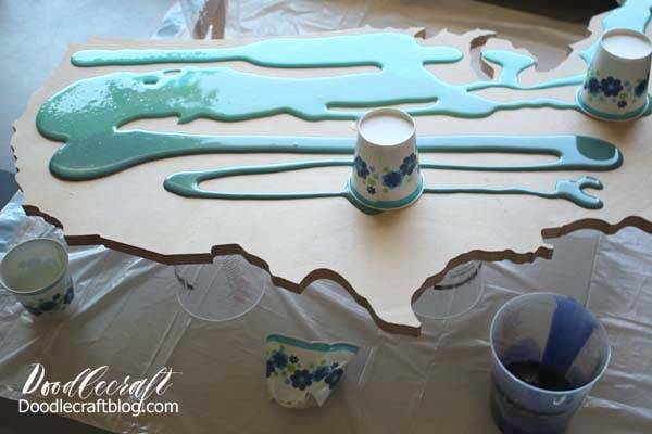 Pouring out the resin/paint for an Ocean Resin Pour on USA Cutout DIY tutorial to make home decor look like the waves of the ocean in ombre shades of blue.