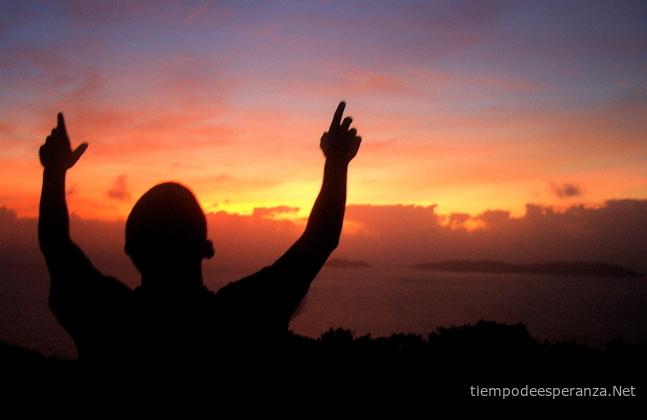 Hombre mirando al cielo levantando sus manos en la atardecer