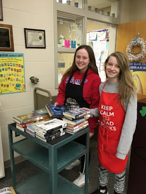 two students with apron and cart with books