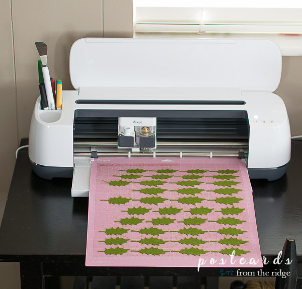 felt holly leaves being cut by cricut machine
