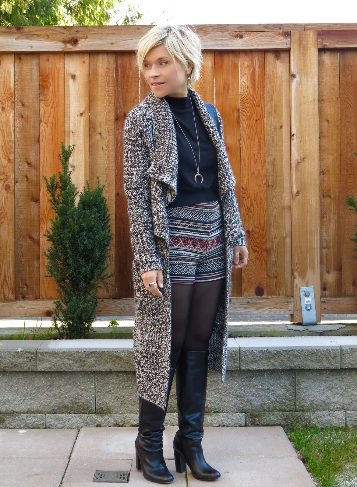 styling embellished shorts with tights, knee boots, and a long cardigan