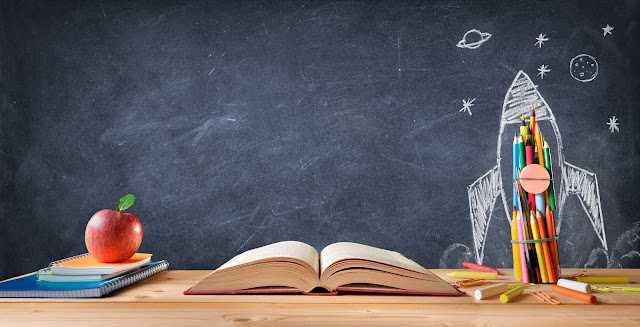 Blackboard with a pile of books, apple, open book and pens in the forefront, a chalk drawing of a rocket sits behind the pen pot