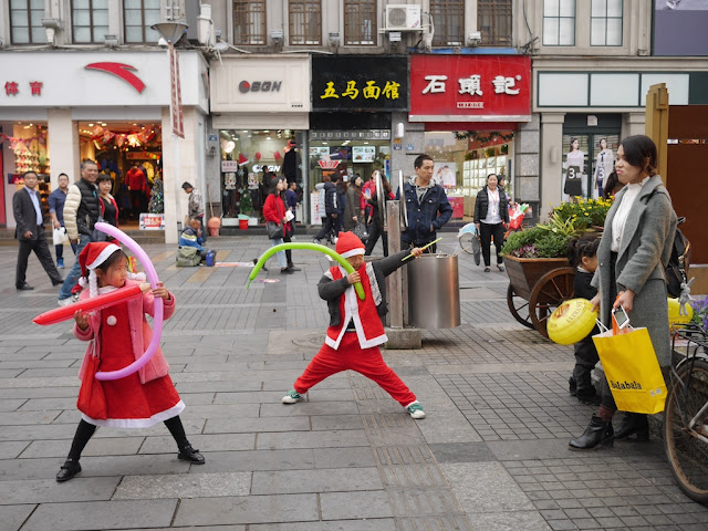 boy and girl wearing Santa and Mrs. Clause outfits pretending to hold weapons aimed at their mother