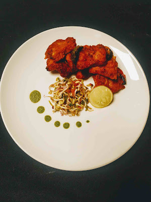 Serving fish Tikka with sprouts salad, green chutney and lemon wedges