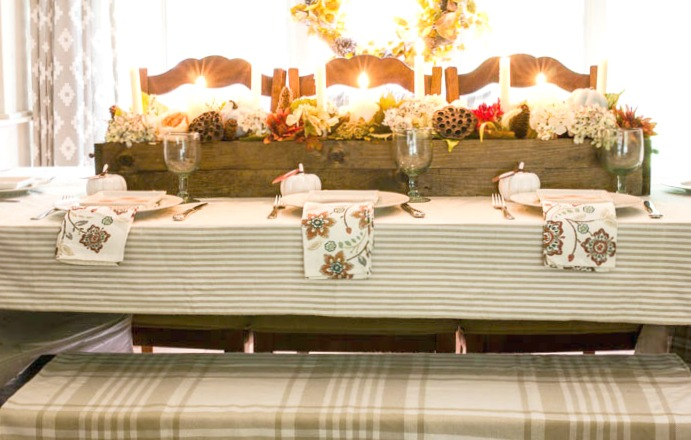 Fall table setting in dining room with neutral striped tablecloth and plaid throw