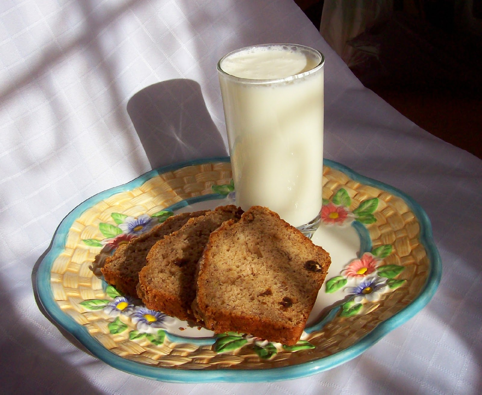 Sliced Banana Date Bread with a tall glass of milk.