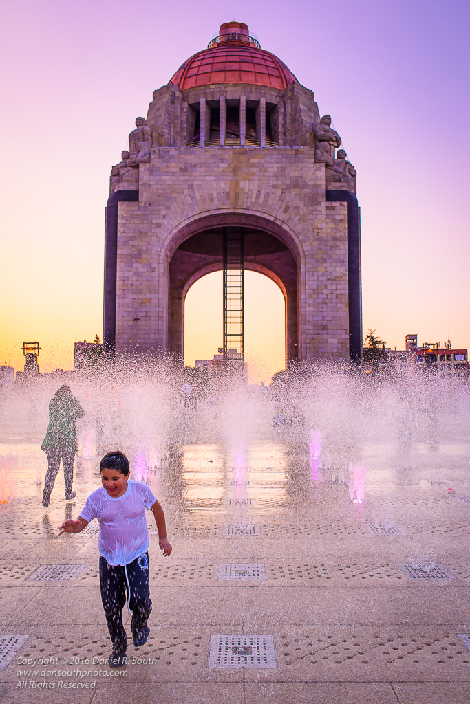 a photo of a child running through a fountain in mexico city
