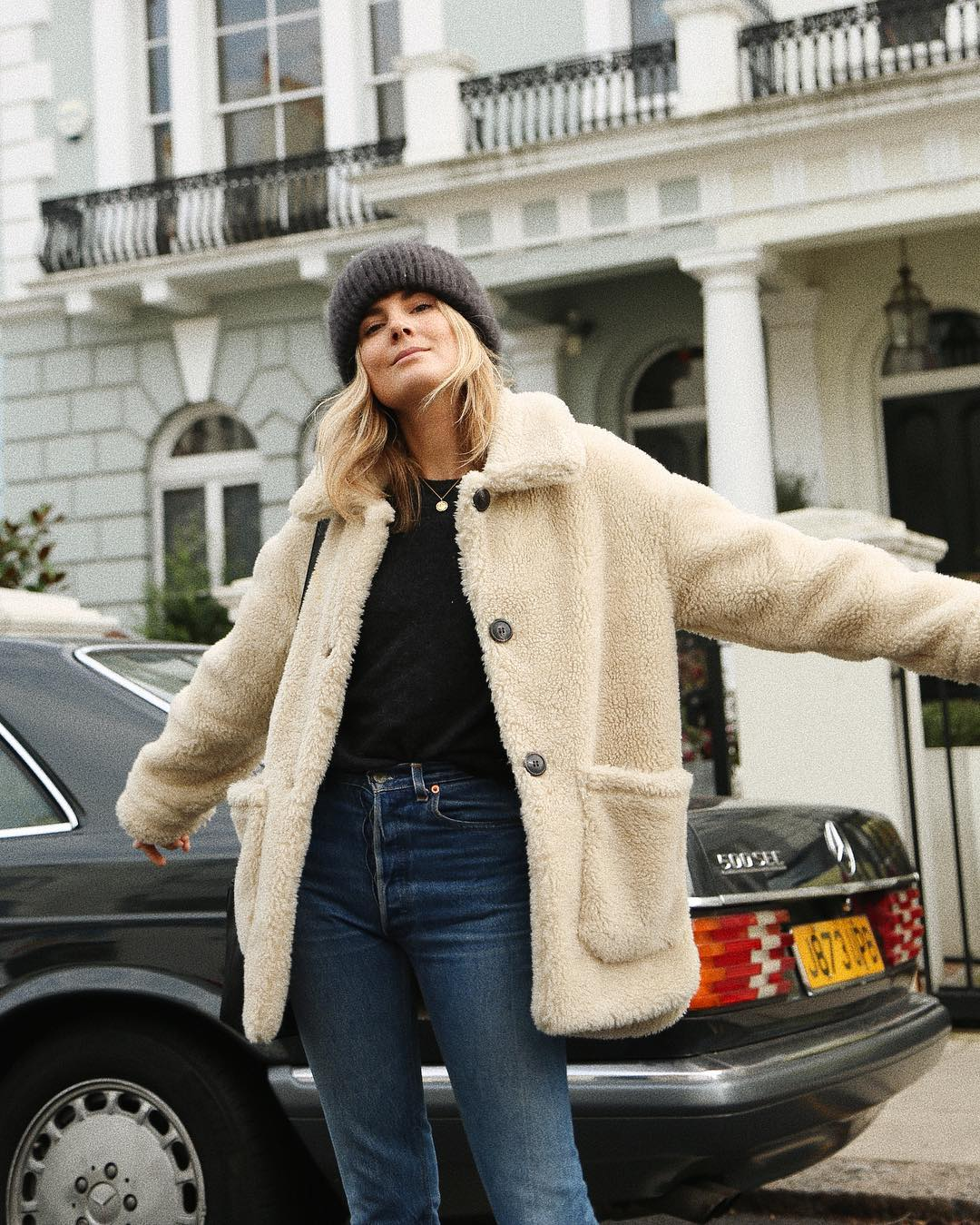 19 Teddy Coats We're Loving This Winter — Lucy Williams in a Beanie, Beige Coat, Black Top, and Jeans