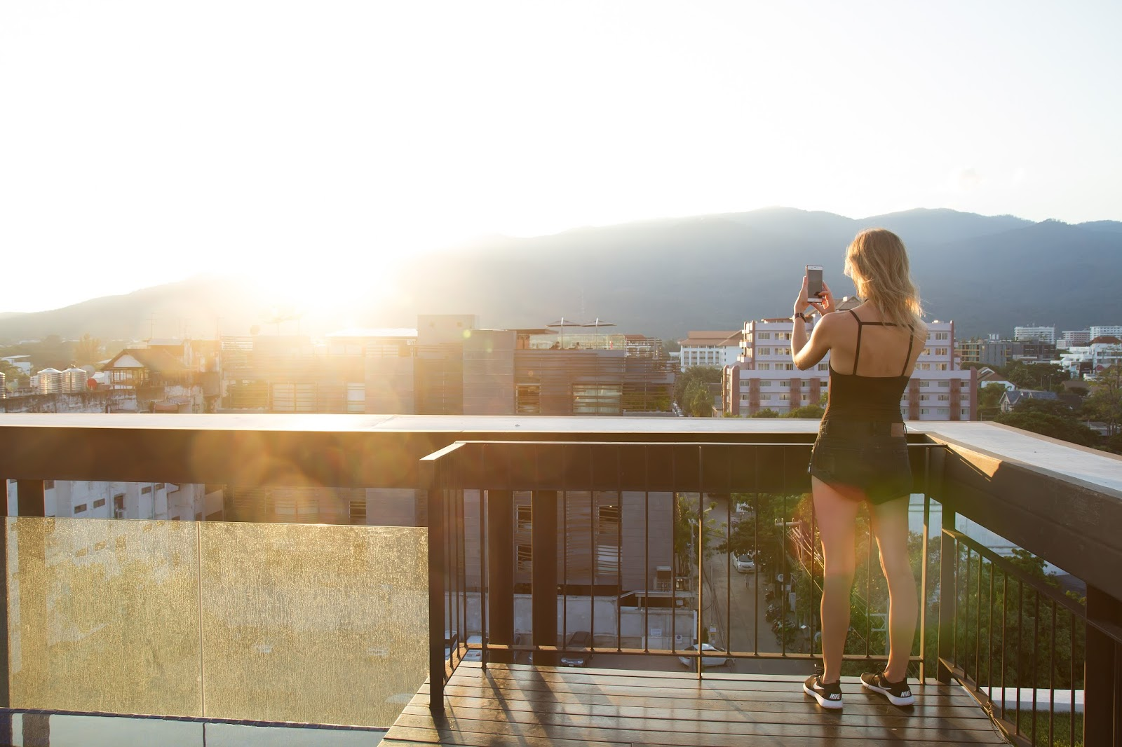 Fashion/Travel blogger and digital nomad, Alison Hutchinson of Styling My Life, is wearing a black Topshop bodysuit and black One Teaspoon Bandits with NIke Trainers on a rooftop overlooking Chinag Mai