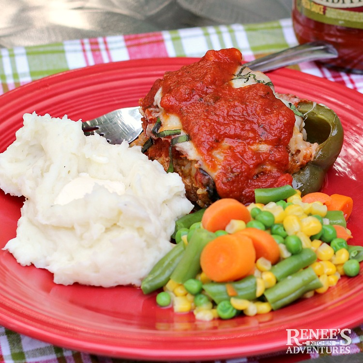 Italian Sausage Stuffed Peppers with Pasta Sauce by Renee's Kitchen Adventures on a red plate with a fork, mashed potatoes, and mixed vegetables.