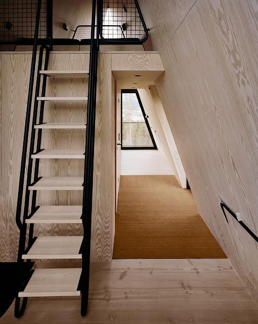 escalera al interior de la cabaña con acabados de madera