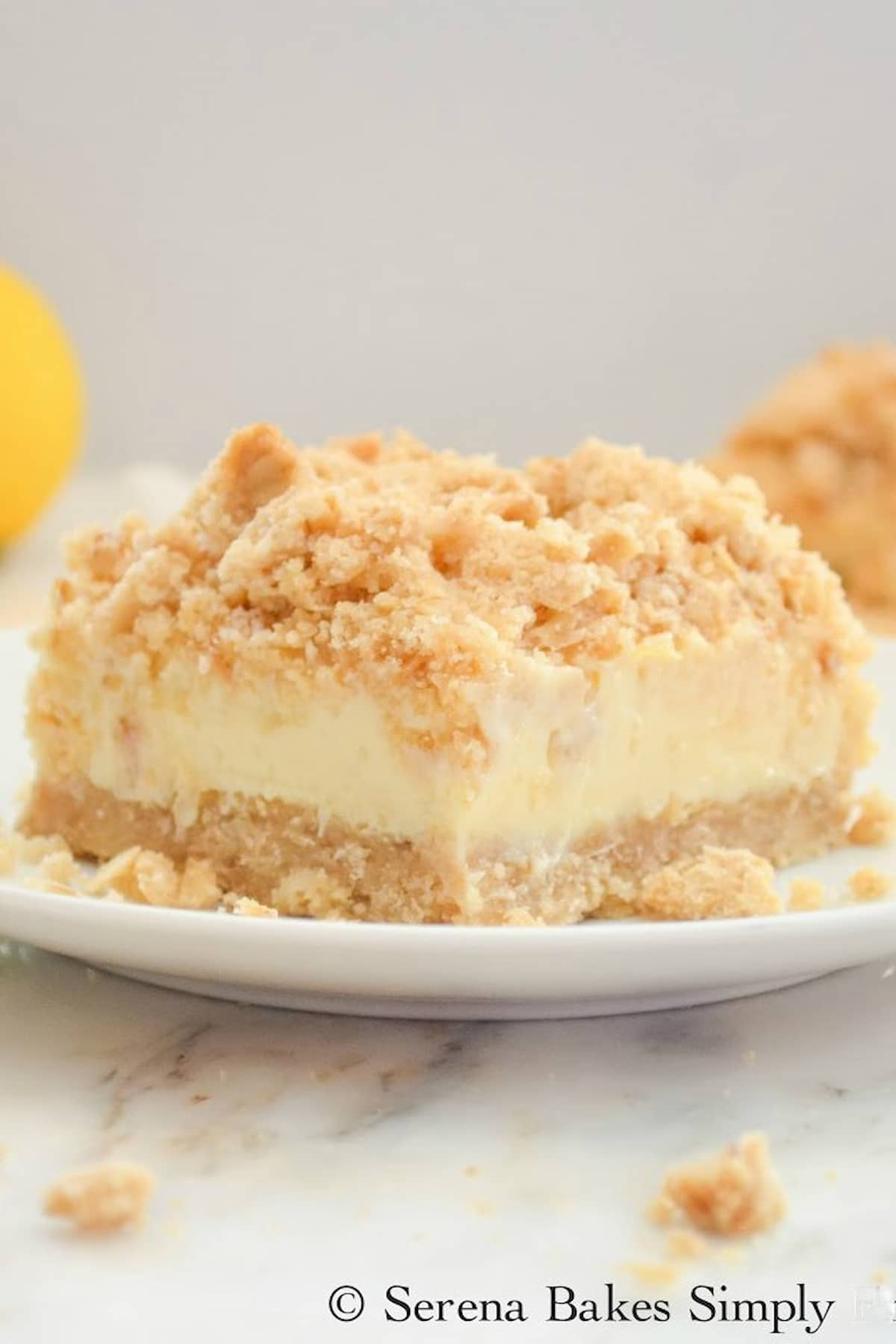 A slice of Creamy Lemon Cheesecake Crumb Bars on a white plate.