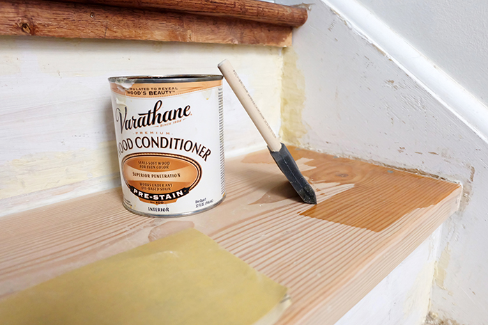 applying wood conditioner to pine wood