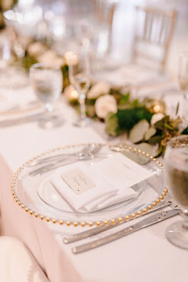 clear chargers with gold beading at wedding guest tables
