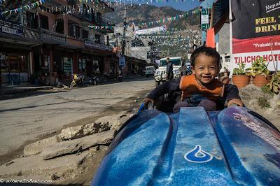 kid in kayak in nepal, prayer flags, child cute, Upper Marsyangdi Himalayas WhereIsBaer.com Chris Baer