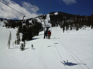 Exterior ski area with blue skys.  People riding on a chair lift.