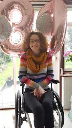Hannah sitting in her manual wheelchair. She is wearing a multi coloured striped jumper and a mustard scarf. She has a large rose gold three and a zero balloon behind her. She is smiling at the camera.