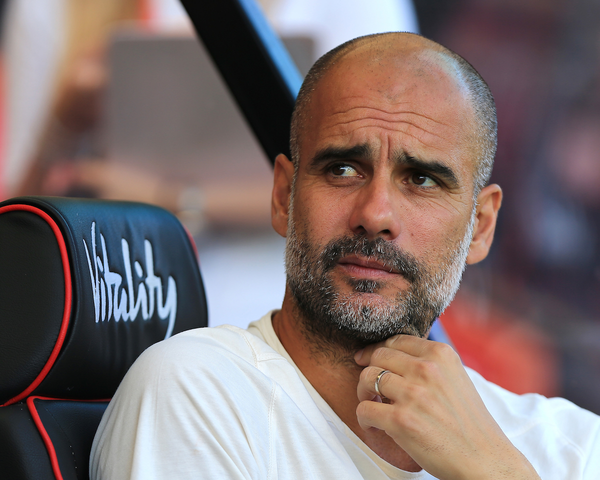 Pep Guardiola sits on the bench