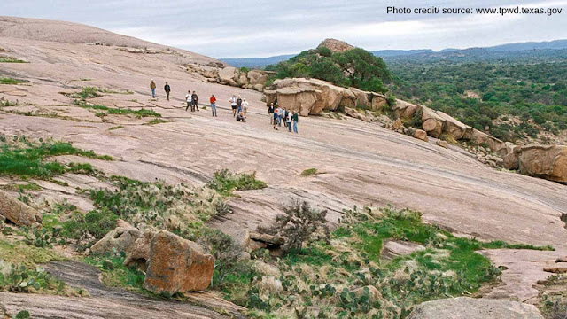 a group of hikers moving towards the summit of Enchanted Rock