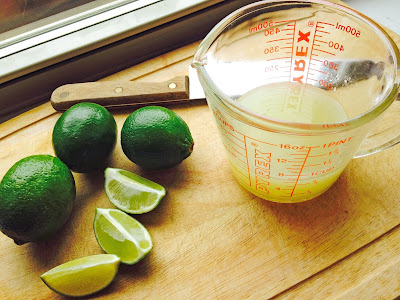 Limes with measuring cup of lime juice