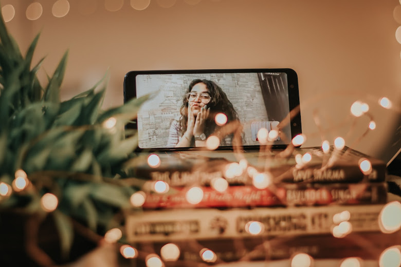 A picture of a girl on phone which is kept on top of a stack of books and a plant pot at the left side and fairy lights interlacing the books and plant