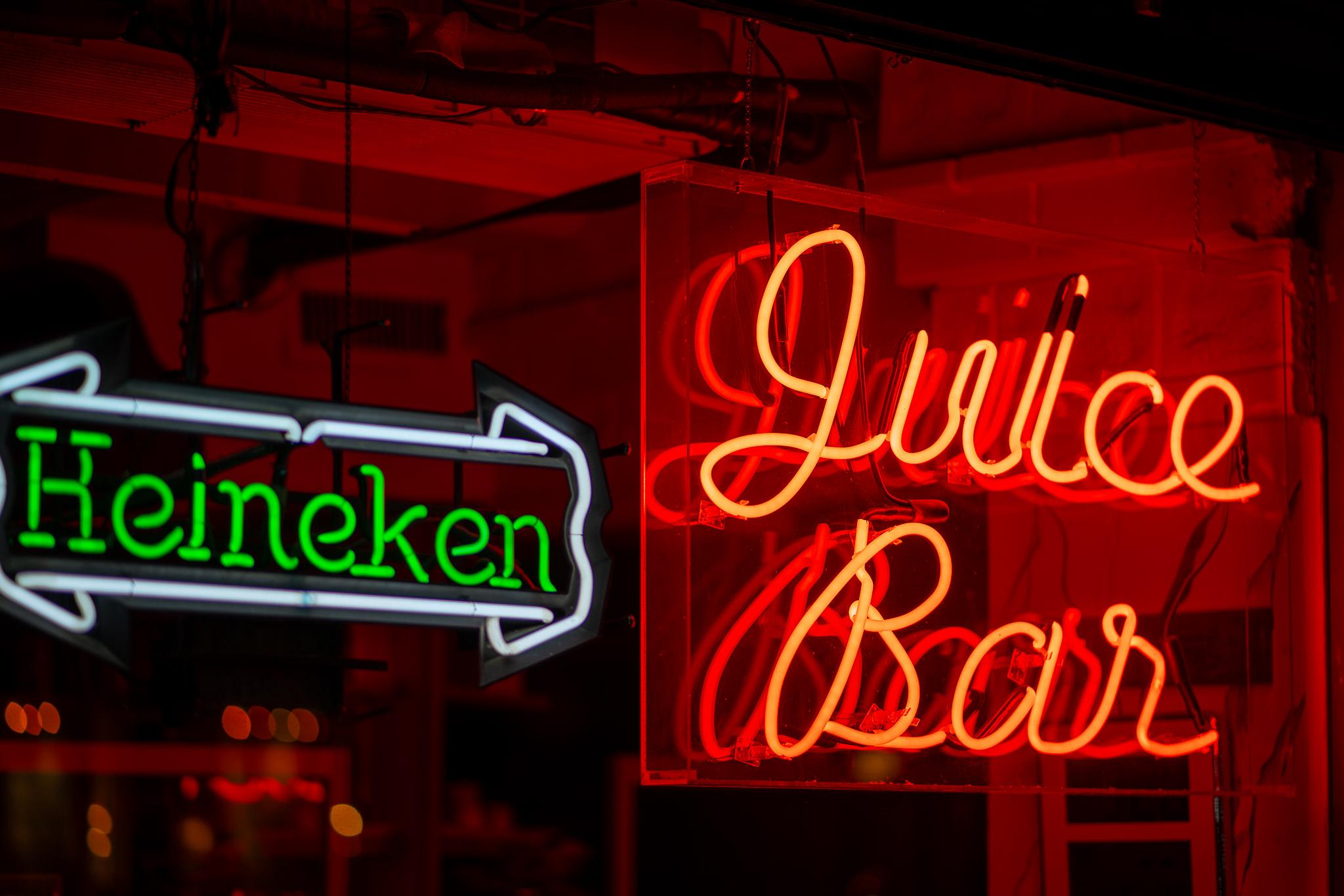 a photo of a neon sign at a new york juice bar at night