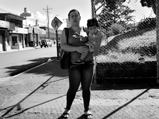 woman holding child on street corner of Puriscal