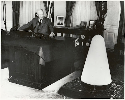 President Dwight D. Eisenhower shown with scale model of Jupiter C Missile nose cone during speech given from the White House, November 7, 1957.