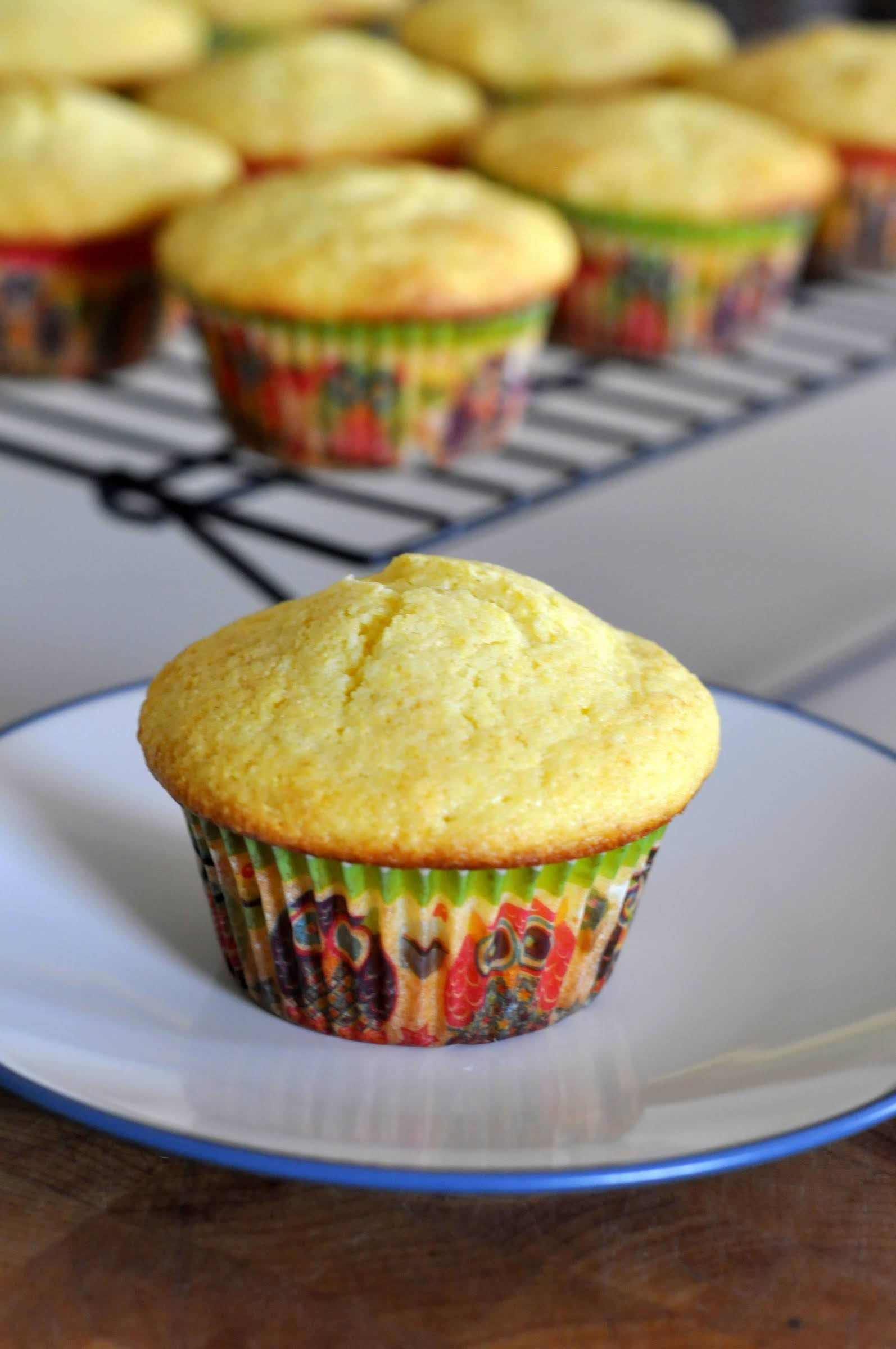 A single honey cornbread muffin sitting on a plate with a cake stand of additional muffins behind it.