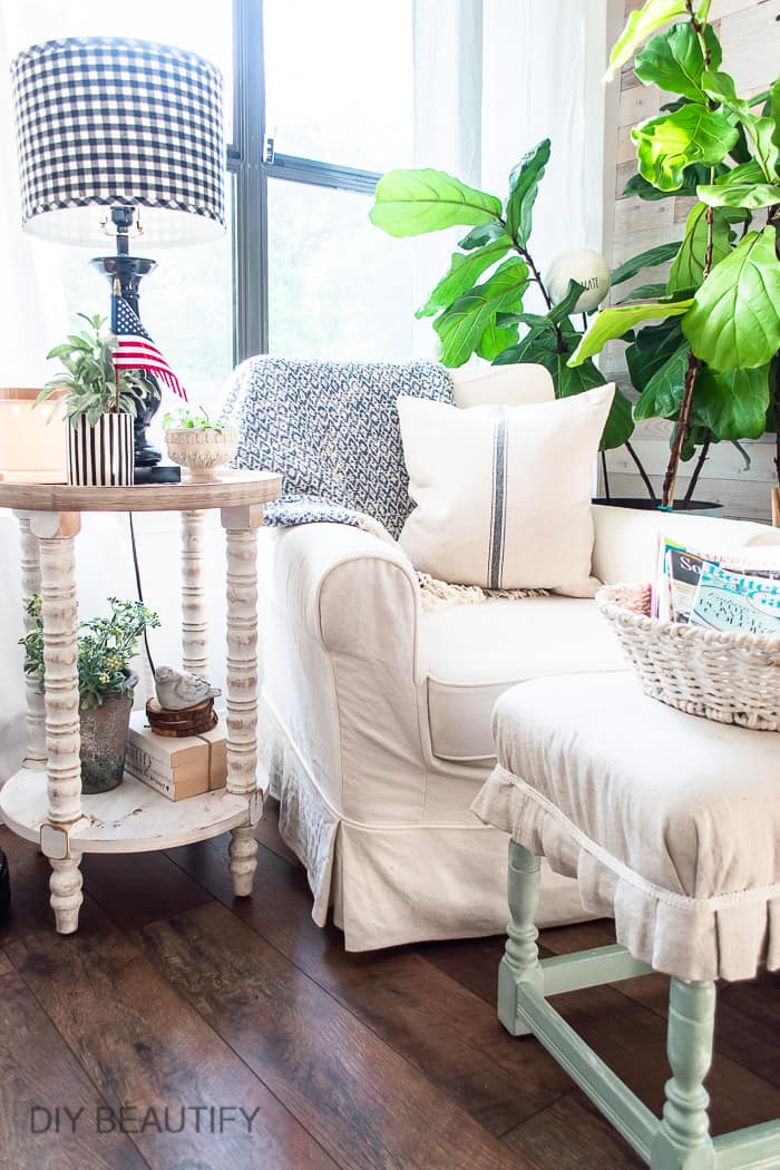 cozy cottage seating with distressed side table and fiddle leaf figs
