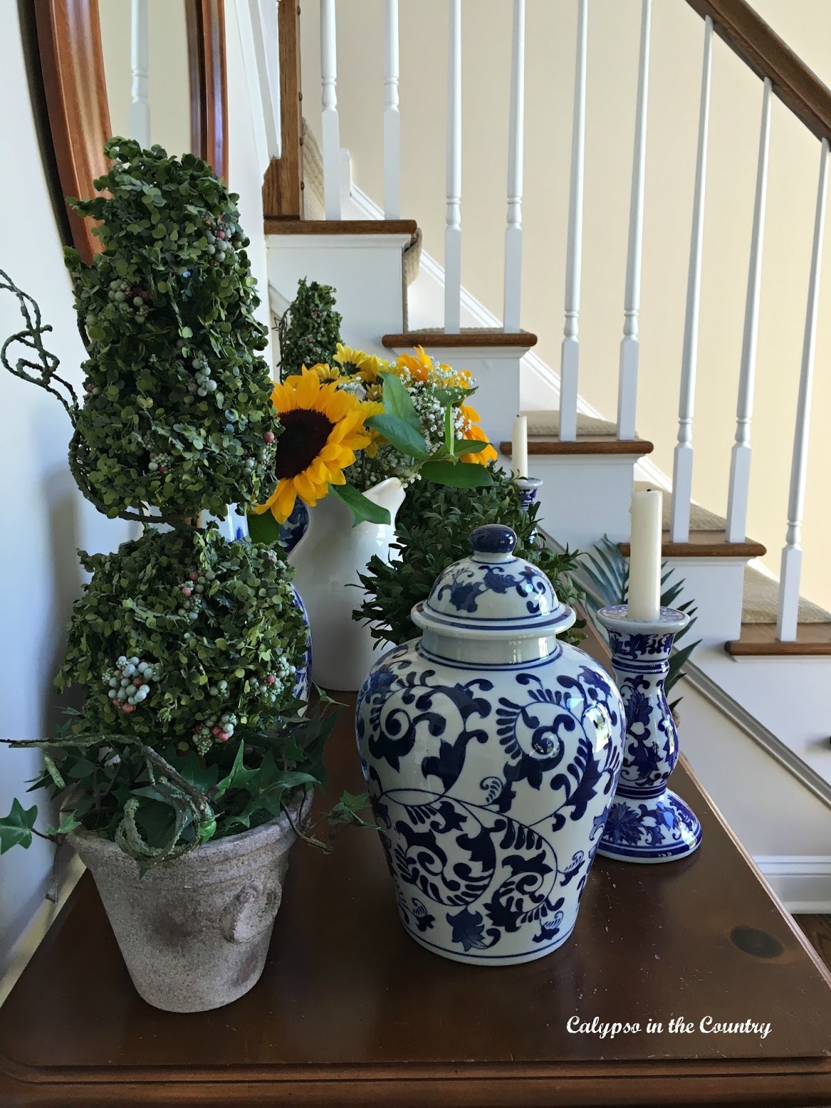 Staircase and foyer table decorated with blue and white