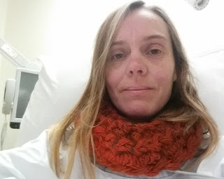 Jodie's head and shoulders. She is in a white room, wearing a white hospital gown and a variegated orange crocheted cowl made of chunky yarn. Jodie's shoulder length hair falls straight down either side of her pale face.  A monitor screen can be seen in the background on the left hand side. The edges of a spotlamp can be seen above Jodie's head at the top right of the picture.