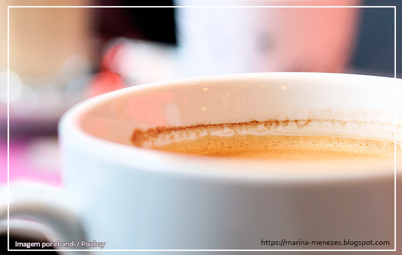 A imagem mostra uma xícara de café no lado direita, cheia com capuccino. A imagem possui foco na borda da xícara, sem ser possível ver o que está ao fundo