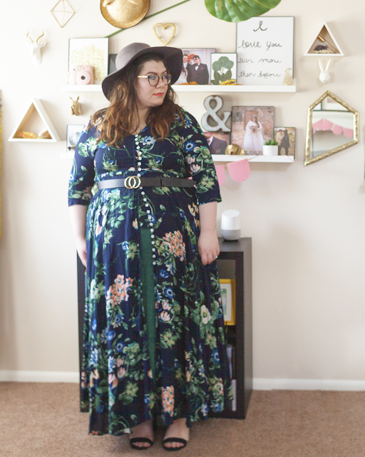 An outfit consisting of a grey wide brim hat, a 3/4 sleeve green and cream floral print on navy blue maxi dress buttoned half way over a green tiered maxi dress and black sandal heels.