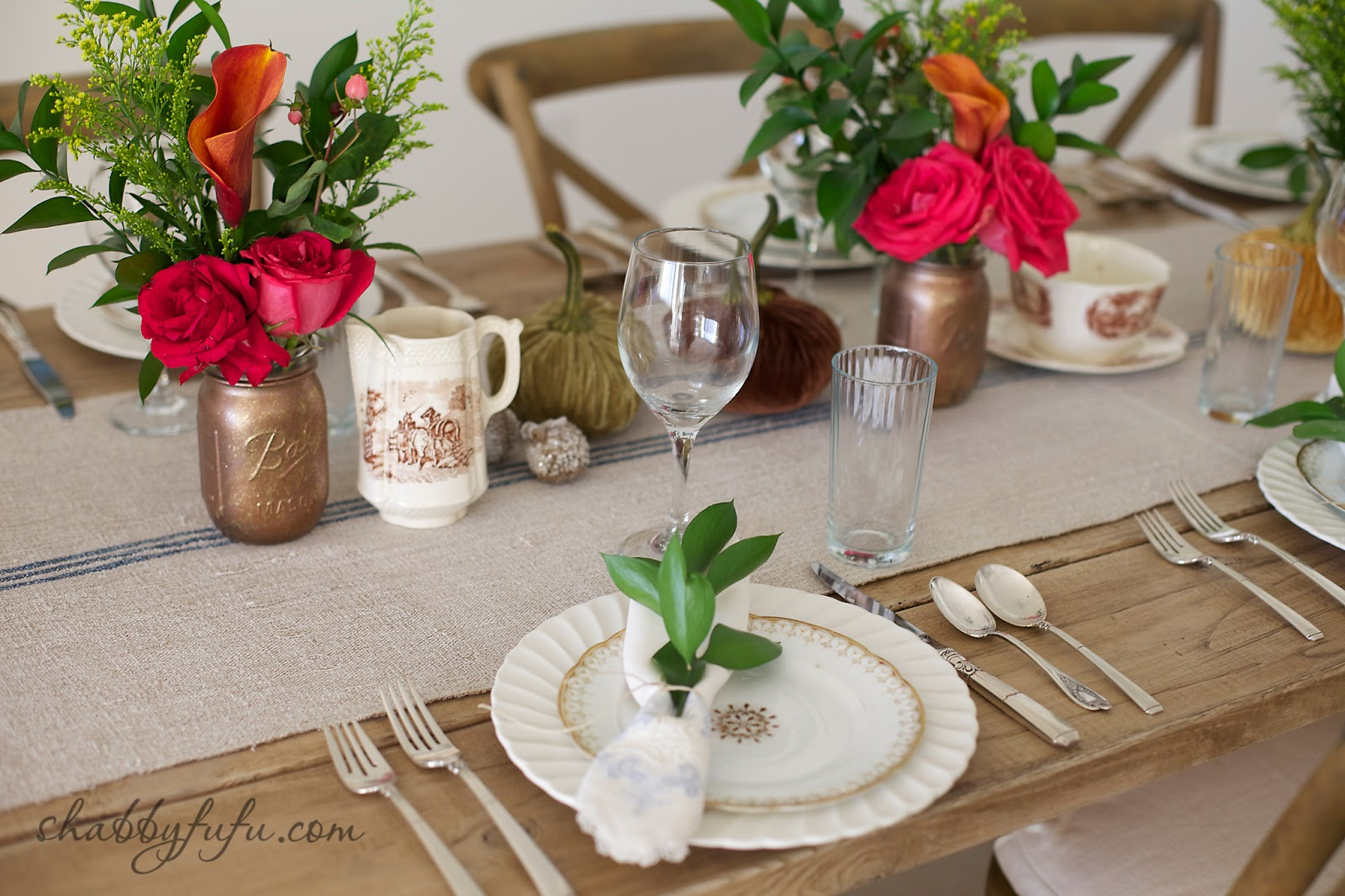 Thanksgiving Beach House decor tablescape with bright flower arrangements and white china